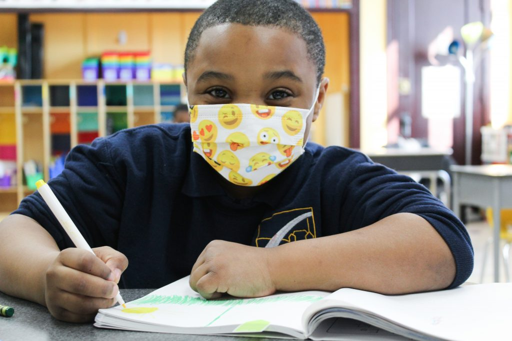 charter school student writing in notebook